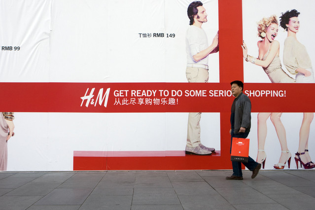 A shopper walks past an advertisement for an upcoming Hennes & Mauritz (H&M) AB store in Beijing, China. Photographer: Nelson Ching/Bloomberg News
