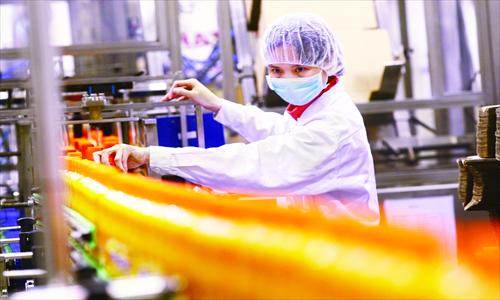 A worker checks bottled Sunquick brand juice on a production line of the new CO-RO FOOD