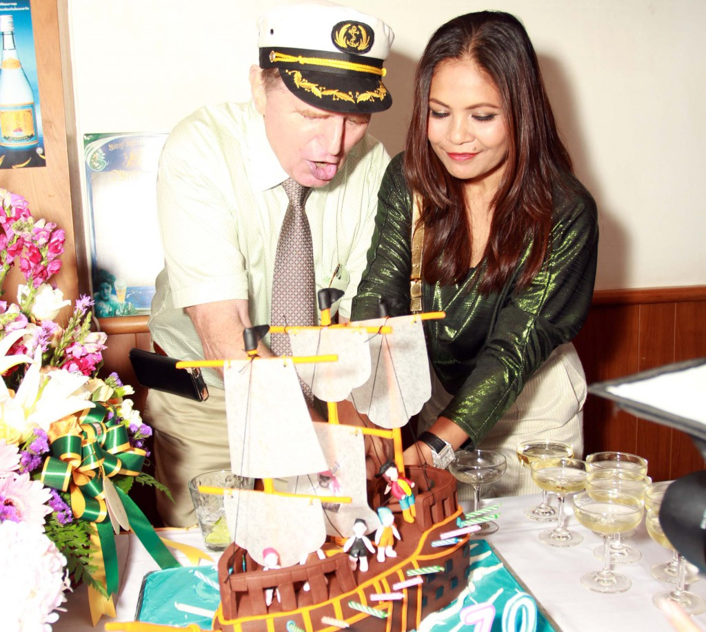 Jorgen with his captain's cap and Khun Tip cutting the birthday cake – an old pirate ship build in cake and chocolate.